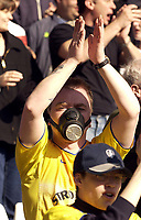 Photo. Jed Wee<br />Liverpool v Leeds United, FA Barclaycard Premiership, Anfield, Liverpool. 23/03/2003.<br />A gas masked equiped Leeds fan contemplates matters away from the Gulf.