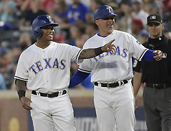 September 12, 2017 - Arlington, TX, USA - Texas Rangers first base coach Hector Ortiz teaches rookie outfielder Willie Calhoun, left, how to celebrate the Rangers way after getting his first major league hit and RBI during the second inning against the Seattle Mariners at Globe Life Park in Arlington, Texas, on Tuesday, Sept. 12, 2017. (Credit Image: © Max Faulkner/TNS via ZUMA Wire)