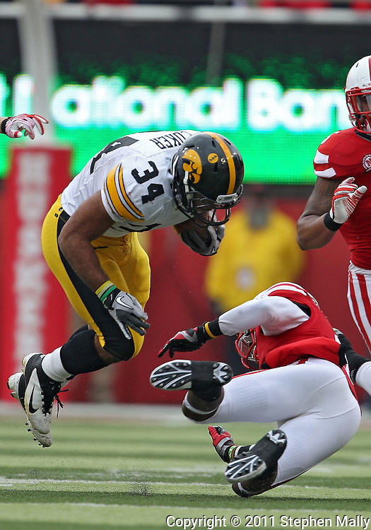 November 25, 2011: Iowa Hawkeyes running back Marcus Coker (34) is tripped up by Nebraska Cornhuskers safety Daimion Stafford (3) on a run during the first half of the NCAA football game between the Iowa Hawkeyes and the Nebraska Cornhuskers at Memorial Stadium in Lincoln, Nebraska on Friday, November 25, 2011.