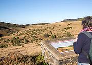 Woman reading information board montane grassland and cloud forest environment Horton Plains national park, Sri Lanka, Asia