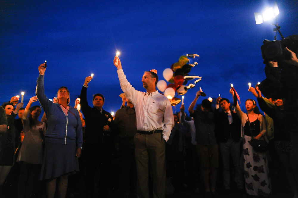 People attending the vigil for slain German exchange student, Diren Dede, on May 2, 2014, at the Fort Missoula soccer field where Dede had played, raise their candles in his memory.