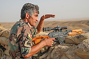 Peshmerga sniper, Sewan (31), scouts the horizon from the Mount Batiwa frontline. Iraqi Kurdistan.