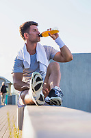 Portrait of young attractive man sitting while drinking energy drink