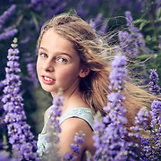 Young girl surrounded by purple flowers.