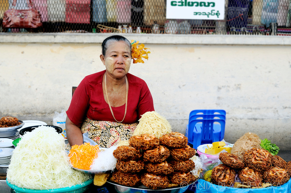 Myanmar/Burma, Yangon. Woman selling burmese snacks in a street food stall.
