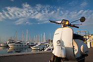 A Vespa motor scooter is parked alongside yachts at the harbor in Cannes, France, on the French Riviera.