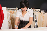 Young fashion designer working at her clothing store