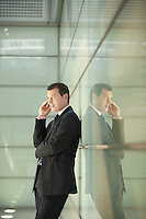 Businessman Using Cell Phone in Office Corridor