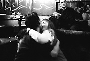Man in a club looking on as two people sit snogging on a sofa, Russia, 2003
