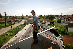 29 August 2006. New Orleans, Louisiana. Lower 9th ward. On the one year anniversary of hurricane Katrina, and most of the area remains derelict and abandoned. However a crew of undocumented Honduran immigrants work in the mid day heat to repair a roof, overlooking the devastation all around them. A small symbol of hope amidst the rubble.<br /> Photo Credit©; Charlie Varley/varleypix.com