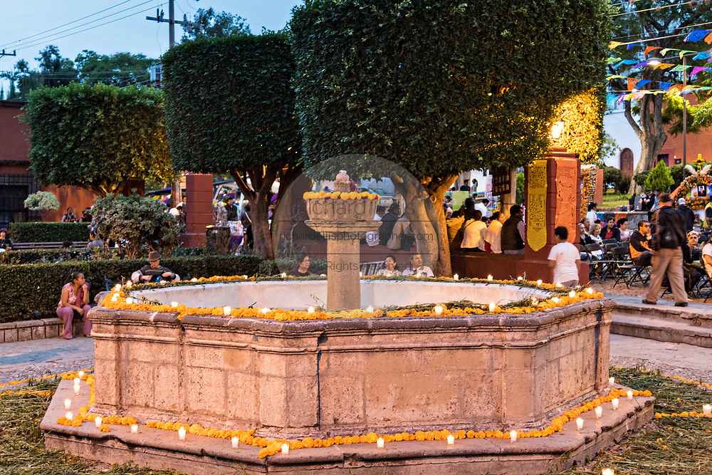 A fountain decorated with candles and marigolds on display outside the San Juan de Dios Church during the Dia de Muertos festival in San Miguel de Allende, Mexico. The multi-day festival is to remember friends and family members who have died using calaveras, aztec marigolds, alfeniques, papel picado and the favorite foods and beverages of the departed.