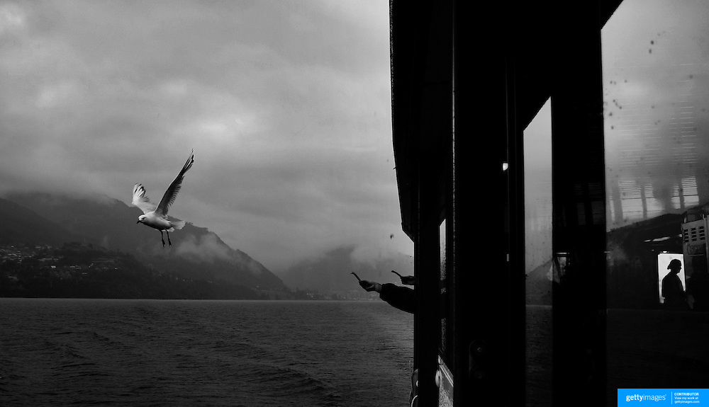 Passengers feed the seagulls while sailing on the Steamboat the TSS Earnslaw on Lake Wakatipu in New Zealand's South Island...You would be forgiven for thinking you'd just stepped out of a time machine while travelling around the South Island of New Zealand.. From the misty shades of grey in the fiord of Doubtful Sound, to the fully operational Steamboat the TSS Earnslaw; the Lady of the Lake on Lake Wakitepo, this beautiful island is a Tardis for tourists!..The South Island of New Zealand is roughly the size of England, but it's population of less than a million people means much of the land remains free from human development. It's breathtaking views, and it's climate, could be likened to a cross between Scotland and Scandinavia, and around every corner is mostly unspoilt natural beauty....The Commercialised resort town of Queenstown is the nerve centre of the islands tourism industry, providing the more adventurous thrill seeker with jet boating, skydiving, bungy jumping, and paragliding to name just a few of the more adventurous activities..Queenstown also provides numerous Lord of the Rings tours into middle earth.. In stark contrast the TSS Earnslaw, The Vintage Steamship which has graced the waters of Lake Wakatipu since 1912 provides daily voyages to Walters Peak and a step back in time for it's passengers. The voyage even includes a good old fashion sing-a-long to songs of yesteryear...Just forty five minutes out of Queenstown the Kingston Flyer, a vintage steam train still operates on 14km of track using two AB Pacific Class steam locomotives built in 1925 and 1927 respectively, although the Flyer's history began much earlier in 1878 when it operated between the main south line and Gore..Fijordland on the south Western side of the Island has some of the world's greatest treks; indeed the Milford Track is often booked up way in advance...