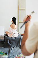 Woman model posing for artist in studio back view