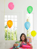 Portrait of young girl (7-9) with birthday presents smiling