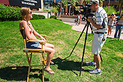 26 MARCH 2012 - PHOENIX, AZ:  JENNA DUFFY, from Glendale, AZ, the organizer of the Phoenix topless protest, gives an interview to a Phoenix TV station after the march Sunday. About 40 people marched through central Phoenix Sunday to call for a constitutional amendment to give women the same right to go shirtless in public that men have. The Phoenix demonstration was a part of a national Topless Day of Protest. Phoenix prohibits women from going topless in public so protesters, women and men, covered their nipples and areolas with tape. The men did it to show solidarity with the women marchers.   PHOTO BY JACK KURTZ