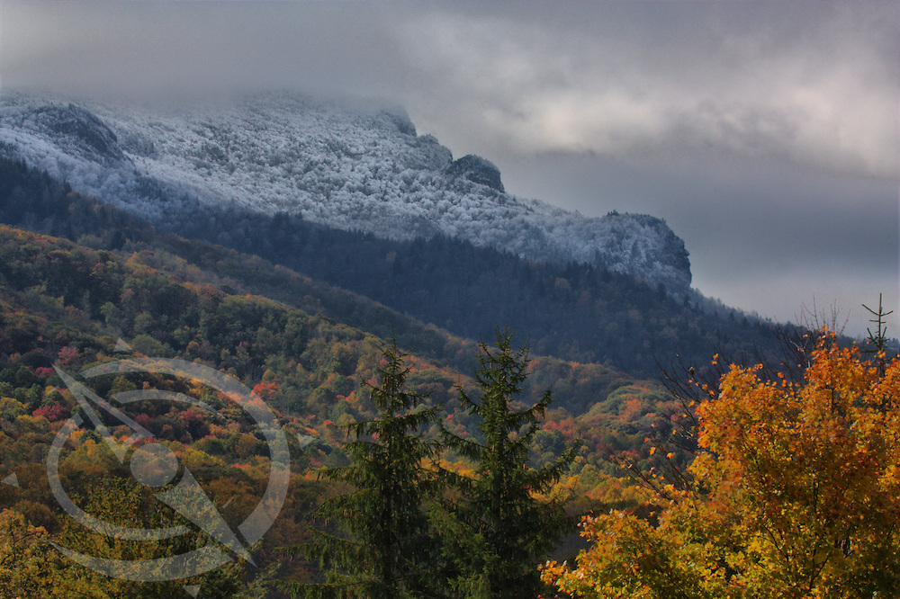 Frost covers the face of Grand Father Mountain as the sun lights the late fall colors.  North Carolina.