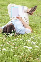 Full length of young man holding book while lying on grass in park