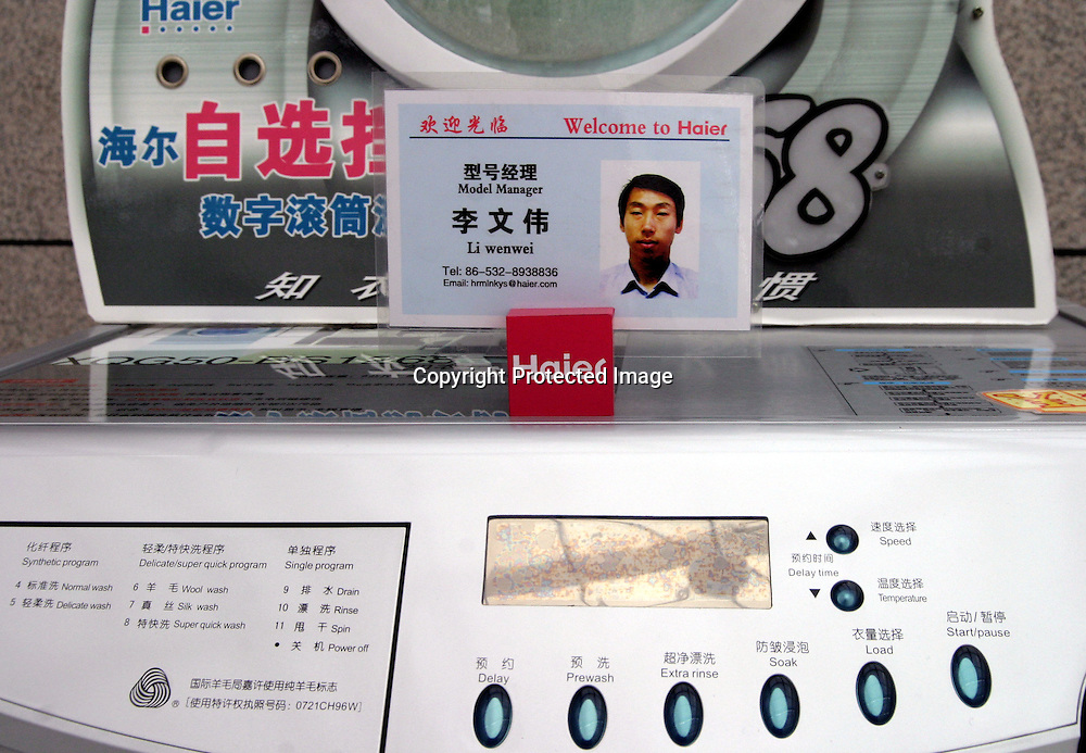 """QINGDAO, MARCH 2005: a portrait of the """" best worker"""" is placed on a washing machine in the Hai'er showroom in Qingdao."""