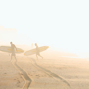 Surfers with longboards make their way through the fog in the early morning at Wrightsville Beach, NC