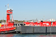 Bouchard Transportation Company red new looking tugboat pushing fuel oil barge through water