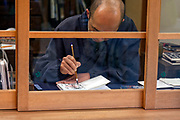 man writing calligraphy with traditional brush Japan