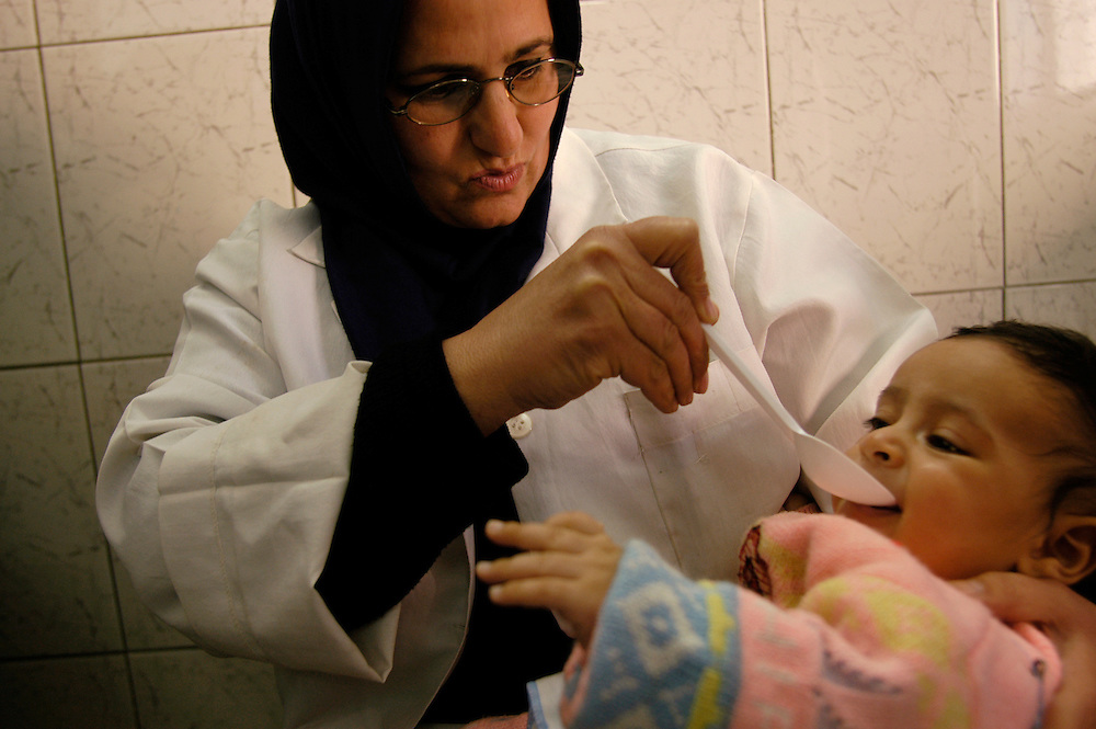 An Iraqi mother spoon-feeds her infant purified water in a Sadr City health clinic.