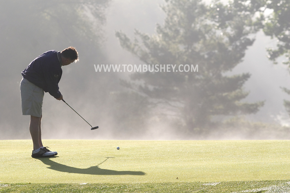 Middletown, N.Y. - A golfer putts the ball on a green during an early-morning round at Orange County Golf Club on Sept. 29, 2006. The grass is wet from dew, and the sun is starting to burn the fog off the course.<br />