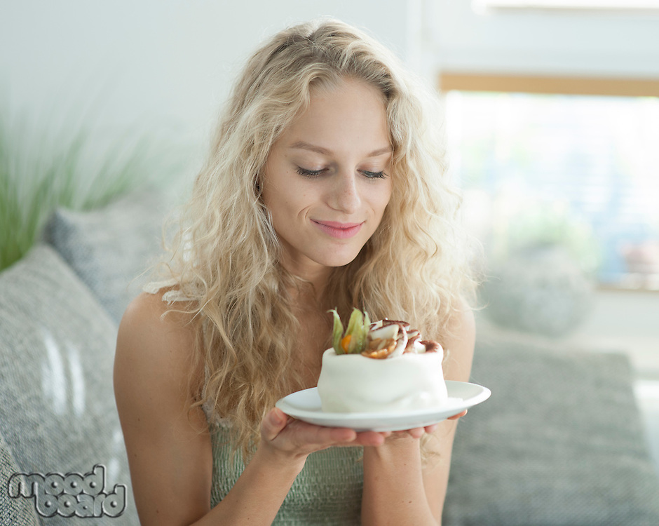 Beautiful young woman looking at tempting cake in house