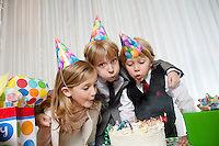 Brothers and sister blowing candles on birthday cake together