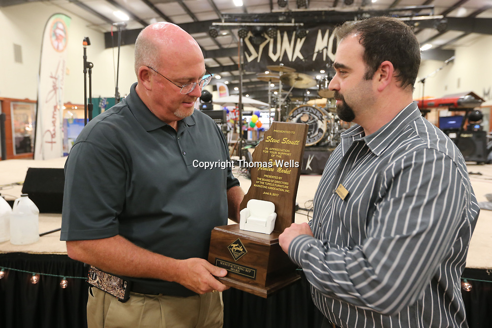 Steve Stoutt, left, accepts the Tupelo Furniture Market Manufactures Award from Adam Cleveland Friday night at the Tupelo Furniture Market.