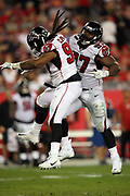 Atlanta Falcons defensive end Adrian Clayborn (99) and Atlanta Falcons defensive tackle Grady Jarrett (97) leap in the air and do a hip bump as the pair of defenders celebrate after sharing a split sack on the Tampa Bay Buccaneers quarterback for a loss of 3 yards on a third down play in the third quarter and forcing a Bucs punt during the 2017 NFL week 15 regular season football game against the Tampa Bay Buccaneers, Monday, Dec. 18, 2017 in Tampa, Fla. The Falcons won the game 24-21. (©Paul Anthony Spinelli)