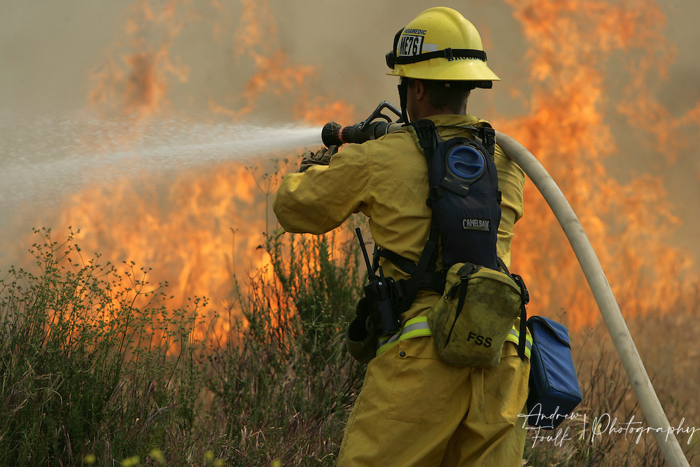 /Andrew Foulk/ For the Californian/.A Cal Fire fire fighter uses a hose to put out the flames from a brush fire that started at around 2pm in French Valley, just North of Keller Road and South of Scott Road. The Fire consumed an estimated 200 acres and caused the closure of Scott, and Winchester Roads.