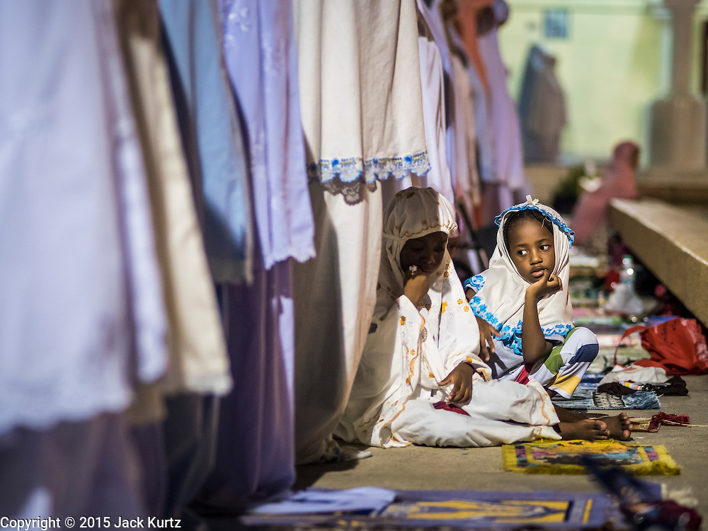 18 JUNE 2015 - PATTANI, PATTANI, THAILAND: A girl plays at her mother's feet during Ramadan services at Pattani Central Mosque. Thousands of people come to Pattani Central Mosque in Pattani, Thailand, to mark the first night of Ramadan. Ramadan is the ninth month of the Islamic calendar, and is observed by Muslims worldwide as a month of fasting to commemorate the first revelation of the Quran to Muhammad according to Islamic belief. This annual observance is regarded as one of the Five Pillars of Islam. Islam is the second largest religion in Thailand. Pattani, along with Narathiwat and Yala provinces, all on the Malaysian border, have a Muslim majority.     PHOTO BY JACK KURTZ