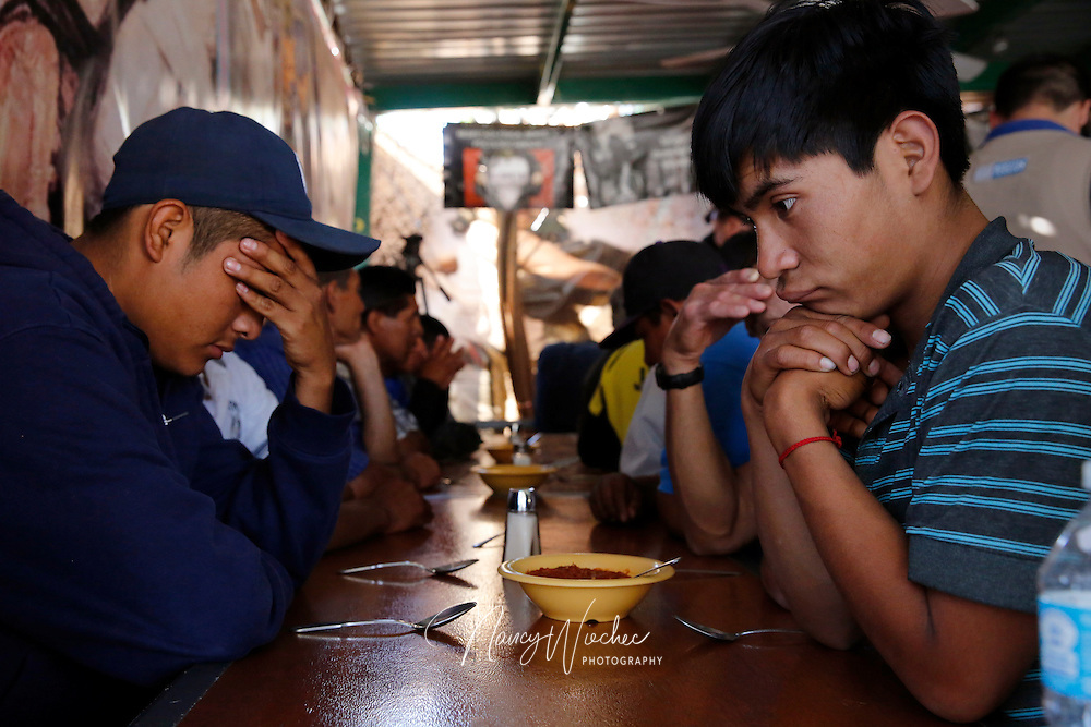 Men pray before eating dinner at the Aid Center for Deported Migrants in Nogales, Sonora, March 31. Dinner that evening was served by visiting U.S. bishops, including Auxiliary Bishop Luis Zarama of Atlanta, pictured at far left. The center, run by the Kino Border Initiative, was one stop the bishops made during their tour of the border area near Nogales. (CNS photo/Nancy Wiechec) (April 1, 2014)