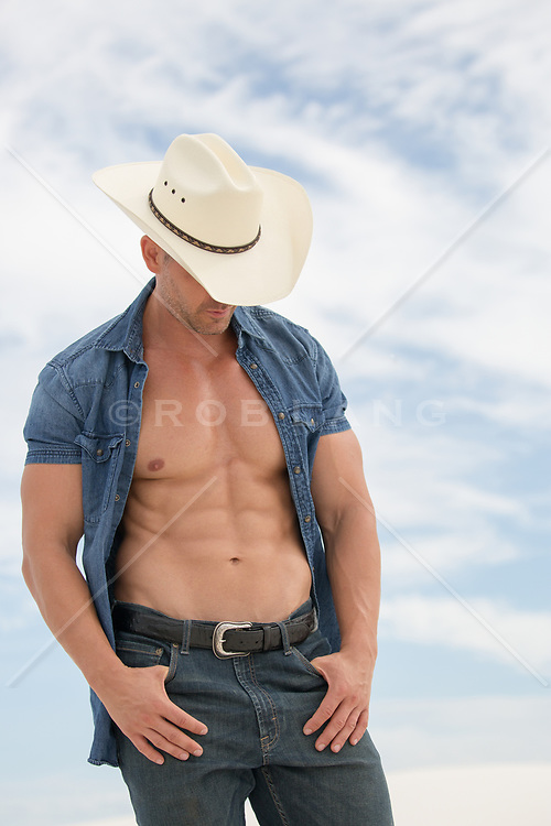 cowboy with open shirt exposing his muscular body
