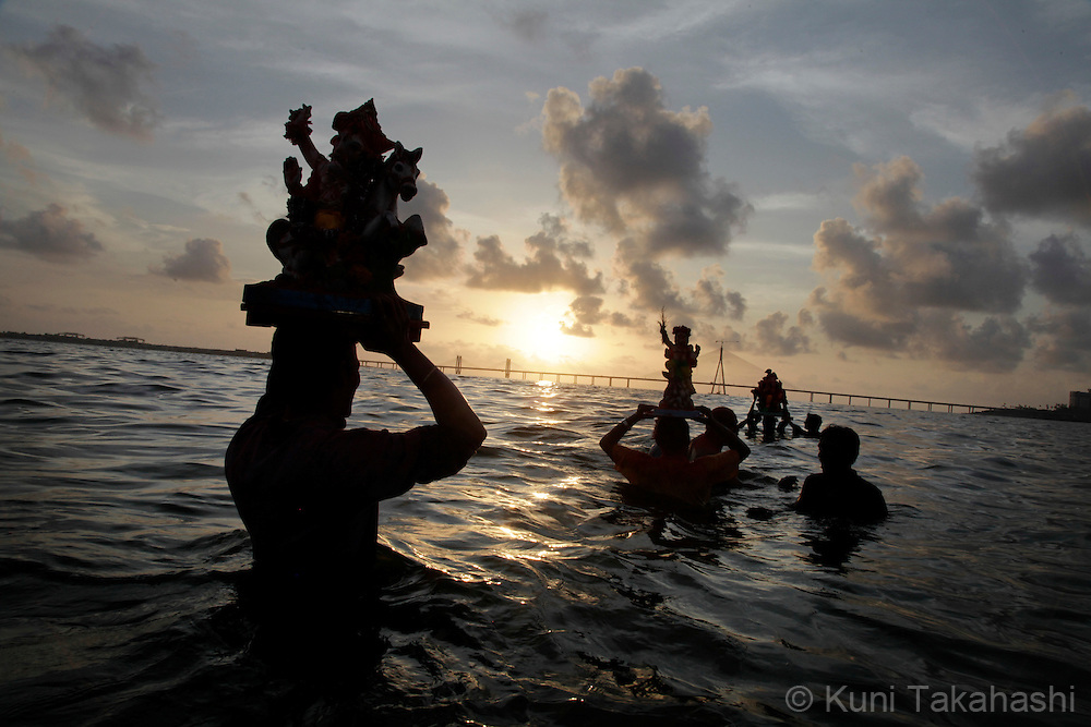 Hindu devotees immerse ganesha idols into the sea in Mumbai, India on Sep 15, 2010 on the 5th day of Ganpati festival. The 10-day hindu festival, celebrating the birthday of Lord Ganesha who is widely worshiped as the god of wisdom, prosperity and good fortune, attracts tens of thousands people.<br /> Photo by Kuni Takahashi