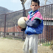 Kosovo, a child playing outside his home.