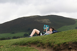 © Licensed to London News Pictures. 06/09/2016. Skipton, UK. A woman reads a book in front of a spectacular backdrop in the hot weather at Bolton Abbey near Skipton in North Yorkshire. Forecasters are predicting the hottest start to Autumn since the 1940s as warm air blows up from the south this week. Photo credit : Ian Hinchliffe/LNP