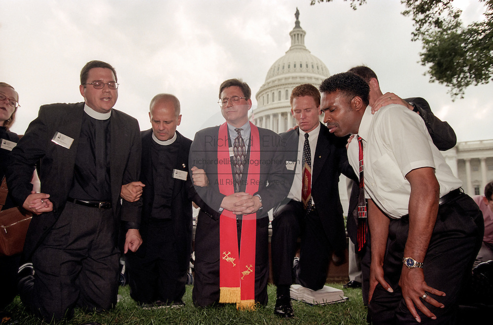 A group of religious leaders hold a prayer vigil outside the US Capitol after a shooting erupted on Capitol Hill July 24, 1998 in Washington, DC. Two US Capitol police officers were killed in the incident, one person wounded and the lone gunmen was wounded and taken into custody.