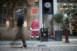 © Licensed to London News Pictures . 25/12/2018 . Manchester , UK . A mural by an unknown artist , featuring Santa Claus holding a bottle of alcohol and urinating against a wall , near to Barton Arcade in Manhester City Centre on Christmas Day . Photo credit : Joel Goodman/LNP