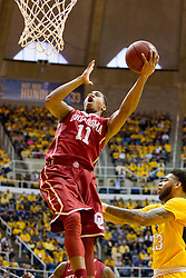 Feb 20, 2016; Morgantown, WV, USA; Oklahoma Sooners guard Isaiah Cousins (11) shoots over West Virginia Mountaineers forward Esa Ahmad (23) during the first half at the WVU Coliseum. Mandatory Credit: Ben Queen-USA TODAY Sports