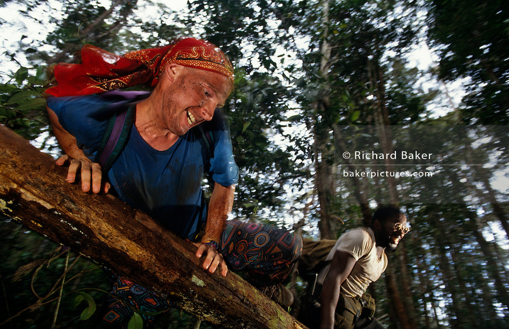 Grinning from ear to ear, young volunteers throw themselves over a fallen tree during a strenuous activity on a Raleigh International expedition in the rainforests of Brunei, Borneo, one of the remotest and most dangerous habitats on the planet. It has been a life-changing experience for them and their new-found friends from all over the world who will have had to raise several thousands of sponsored Pounds for the privilege of spending two months away from a dull, comfortable life at home, rather than building community projects like bridges or schools. Raleigh International is a charity that provides adventurous and challenging expeditions for people from all backgrounds, nationalities and ages, especially young people. Over the last 23 years, 30,000 people have been involved in more than 250 expeditions to over 40 countries.