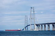 Oil tanker passes under The Great Belt Bridge suspension bridge over Storebaelt view from Halskov, Denmark