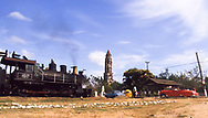 Railroad crossing at Manaca Iznaga in the Valle de San Luis with old steam train, red 1949 Cadillac and 192 meter slave watch tower in the background