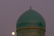 Uzbekistan, Bukhara. Kalon Ensemble. Moonrise behind Mir-i-Arab Medressa.