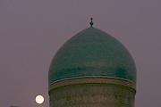 Uzbekistan, Bukhara. Kalon Ensemble. Moonrise behind Mir-i-Arab Medressa.