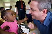 28 November 2008, Ivory Park, South Africa. Ivan Lewis, UK Minister for International Development, greets baby Daphyne Matlabyane at a clinic dispensing ARV drugs.