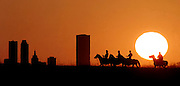 Horseback riders are silhouetted against the Tulsa, OK, skyline at sunset.