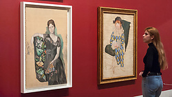 "© Licensed to London News Pictures. 06/03/2018. LONDON, UK.  A staff member views (L to R) ""Portrait of Olga in an armchair (Portrait d'Olga dans un fauteuil"", 1932, and ""Paulo as a Harlequin (Paulo en arlequin)"", 1932, both by Pablo Picasso. Preview of ""Picasso 1932 - Love, Fame, Tragedy"", the Tate Modern's first ever solo exhibition of the work of Pablo Picasso.   More than 100 paintings, sculptures and works on paper covering the year 1932, a pivotal time in Picasso's life, are on display 8 March to 9 September 2018.  Photo credit: Stephen Chung/LNP"