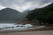 Late in the afternoon, people stand in the sea at Praia do Meio in Trindade, a small town located near Paraty in Brazil's Rio de Janeiro state.